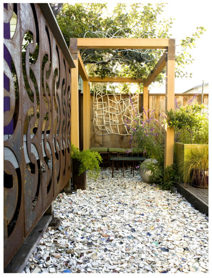 Backyard arbor from recycled products, tumbled dish pathway mulch in Matthew Levesque small space backyard california garden